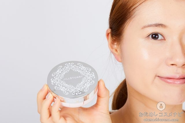 顔の横に『ジルスチュアート ピュアエッセンス フォーエバー クッションコンパクト』のケースを持つ女性
