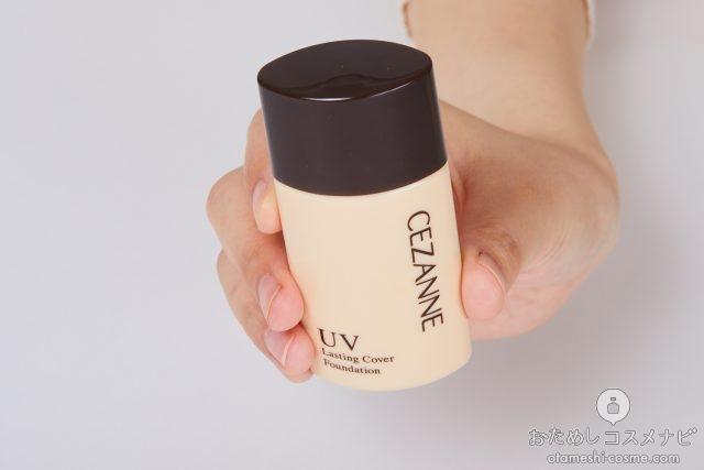 右手に持った『セザンヌ ラスティングカバーファンデーション』のボトル
