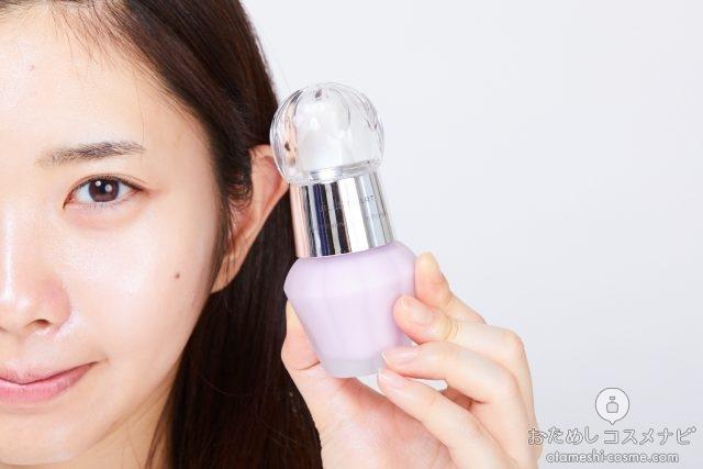 顔の横に『ジルスチュアート イルミネイティング セラムプライマー』の02aurora lavenderを持つ女性