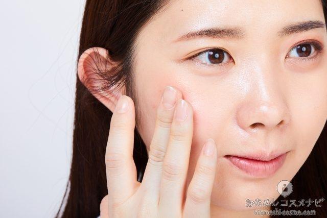 指でハイライトカラーを頬にのせる女性