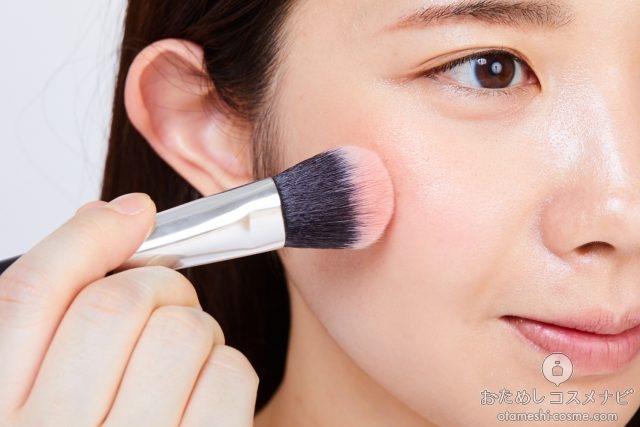 チークブラシを使って『NARS オーバーラスト チークパレット』のチークを頬にのせる女性