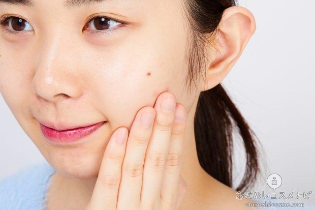 顔にスプレーした化粧水を手でなじませる女性