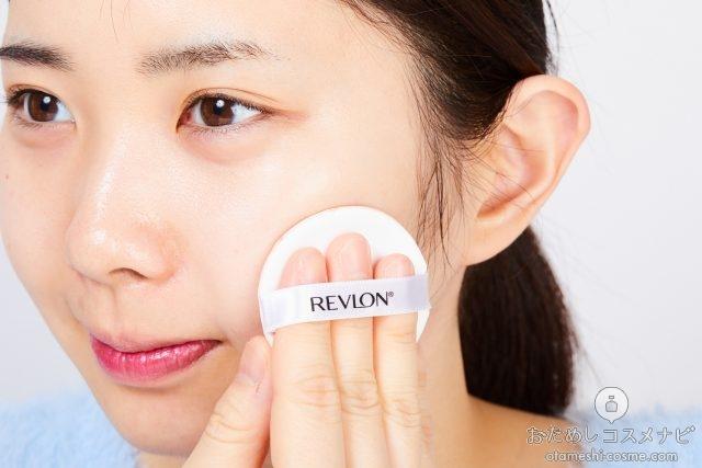 付属のパフで左頬にファンデーションを塗る女性