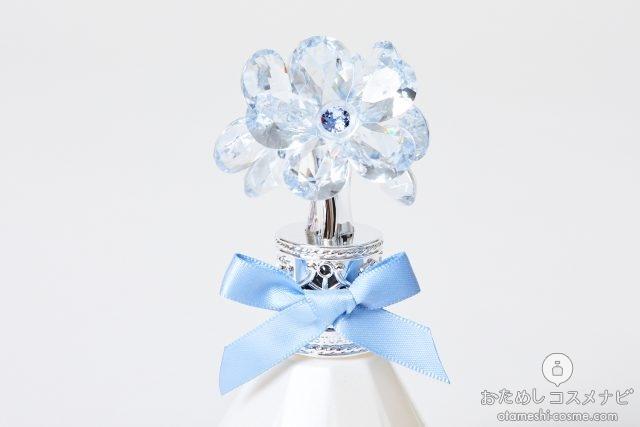 花の飾りがついた『ジルスチュアート クリスタルブルーム サムシングピュアブルー オードパルファン』のキャップ部分