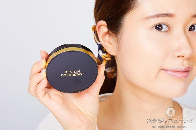 顔の横に『レブロン カラーステイ クッション ロングウェア ファンデーション』のコンパクトを持つ女性