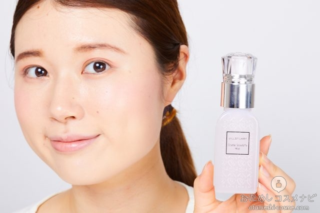 『ジルスチュアート クリスタル グロウ&フィックス ミスト』のボトルを顔の横に持つ女性