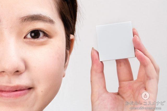 顔の横に『ディエムクルール カラーブレンドグローアイカラー』のケースを持つ女性
