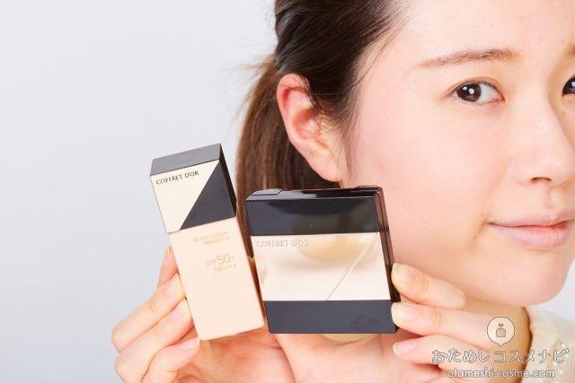 顔の横に化粧品をもつ女性
