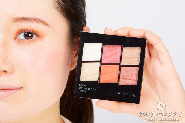 顔の横に化粧パレットを持つ女性