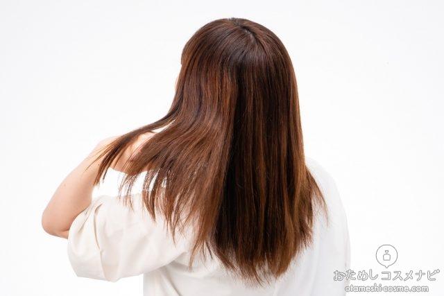 髪をふりはらう女性の後ろ姿